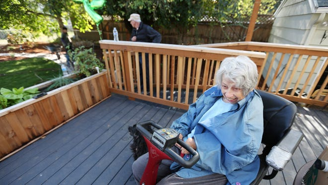 Connie Lee smiles as a crew from DeSantis Landscapes helps the Englewood neighborhood finish its outdoor home makeover for her Saturday, Oct. 24, 2015, in Salem, Ore. Lee has a severe case of rheumatoid arthritis. She uses a power mobility scooter to get around and is unable to tend to her neglected yard in northeast Salem.
