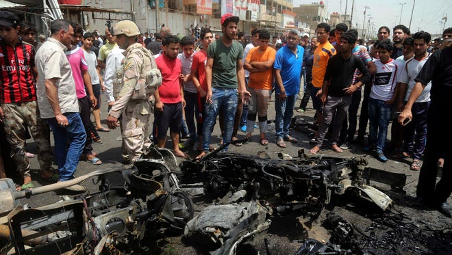 Security forces and citizens inspect the scene after a car bomb explosion at a crowded outdoor market in the Iraqi capital's eastern district of Sadr City, Iraq, Wednesday, May 11, 2016.