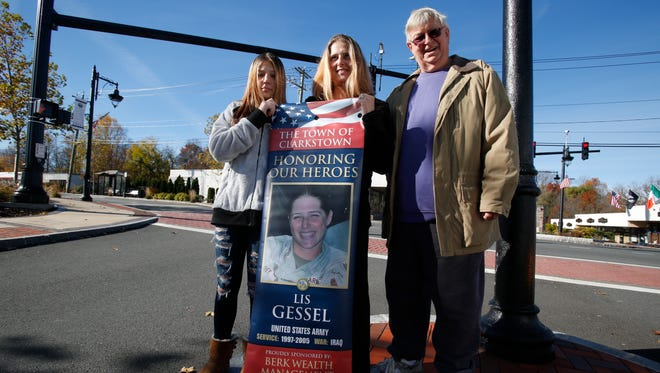 Lis Gessel of New City, along with her daughter, Victoria Richey, 14, and father Rudy Kronbichler, hold a banner  what will be placed on Main Street in New City that will honor Gessel's service in the U.S. Army and her tour in Iraq, on Nov. 10, 2016.