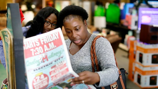 Vicky Cunningham, right, and daughter San'torias Harris search for deals at Cowboy Maloney's Electric City during Black Friday sales in Jackson.