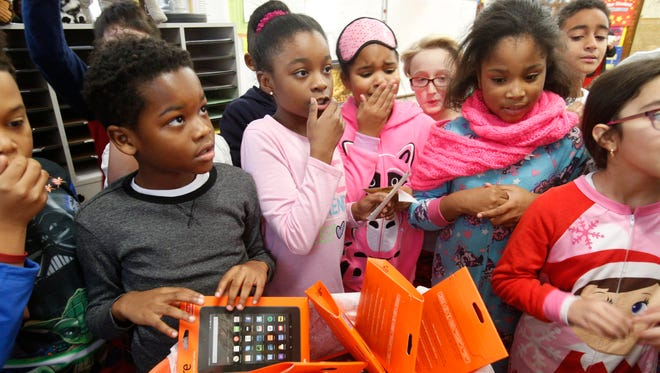 Children look at the tablets donated to the fourth-grade class at Pennington Elementary School in Mount Vernon.