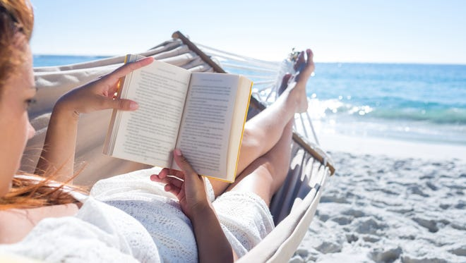 Brunette reading a book while relaxing at the beach.