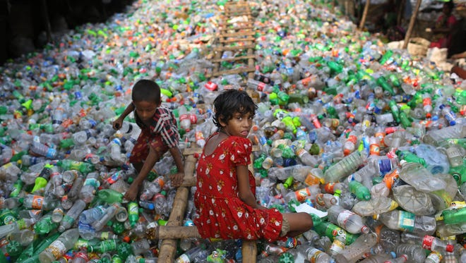 A Bangladeshi girl looks into the camera as she works at a plastic recycling factory as a boy plays on a heap of bottles in Dhaka, Bangladesh in this 2014 file photo. Scientists the University of Portsmouth in the U.K. believe they might have found a solution for plastic bottle waste.
