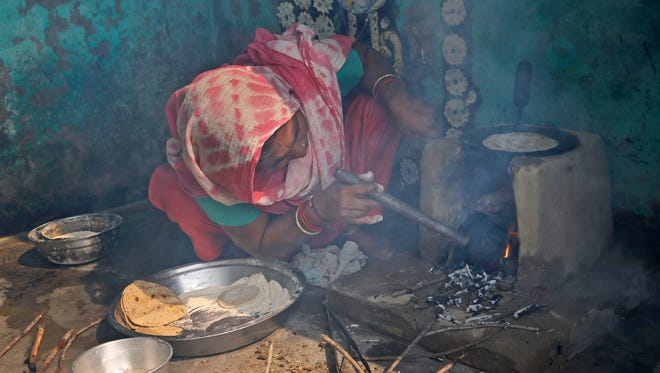 In this Oct. 19, 2015 photo, Indian woman Kamlesh blows air through a pipe to kindle the flames of a crude clay cookstove as she prepares roti or Indian bread at her house in a village near Bulandshahr, Uttar Pradesh state, India. Kamlesh is one of hundreds of millions of Indian housewives who, with the simple act of cooking family meals, fill their homes every day with deadly airborne pollutants. The constant exposure to indoor air pollution kills some 4.3 million people every year across the world - 30 percent of them in India.