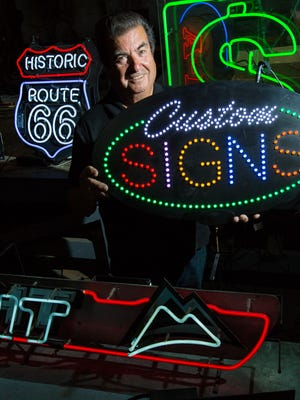 Larry Tafoya, owner of Fluorescent Signs, Inc., is pictured with signs made at his shop on Monday, May 16, 2016.
