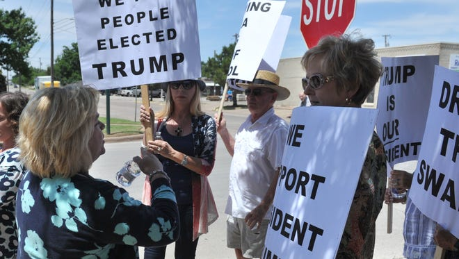 Times Record News Editor Deanna Watson (left) handed out bottled water Thursday to a group of protesters protesting outside the newspaper office located on Lamar Street. The small group of people were protesting the newspaper for its coverage of President Donald Trump.