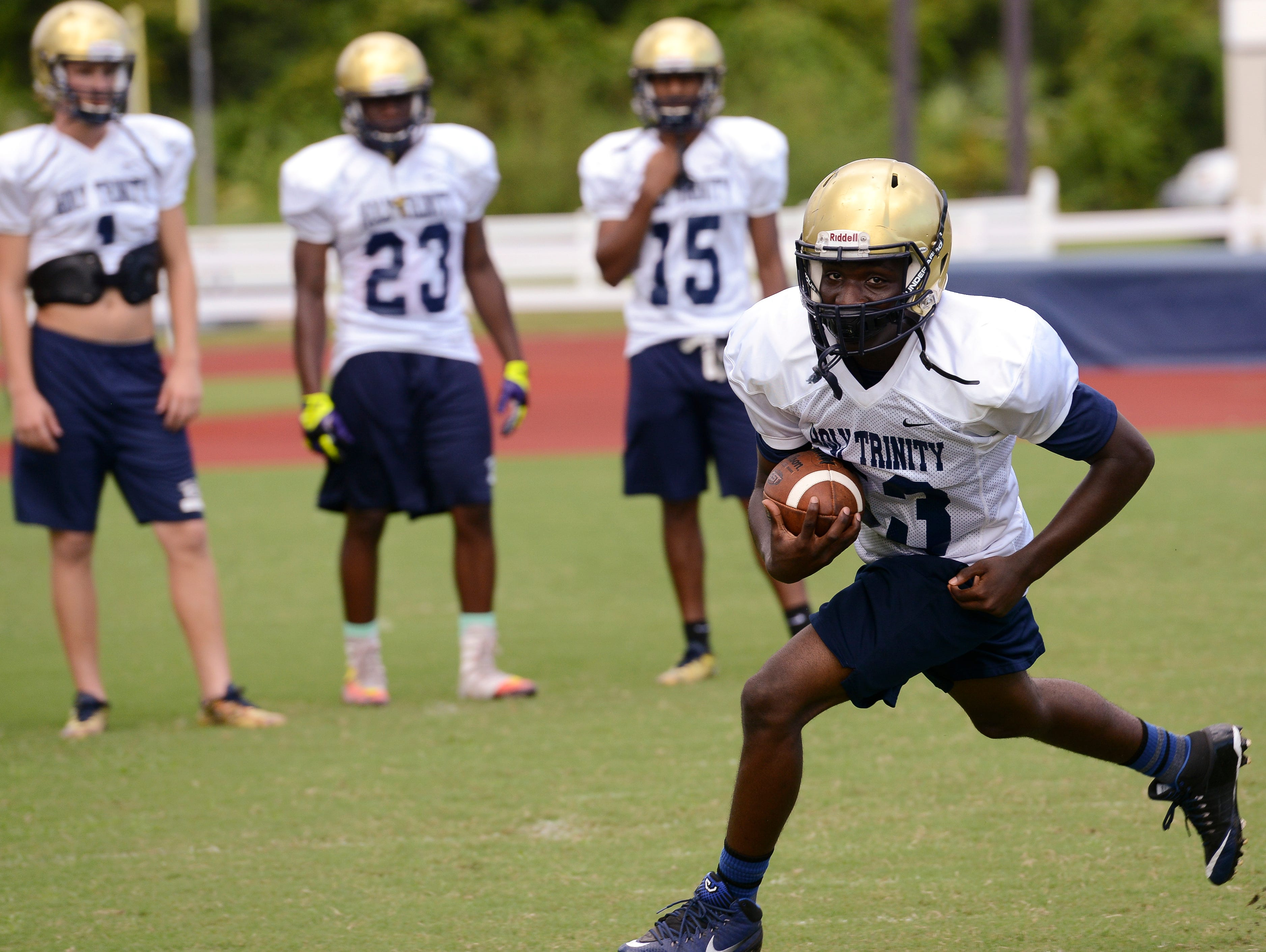 LaAnthony Valentine carries the ball for the Holy Trinity football team in practice. His brother plays at Melbourne Central Catholic.