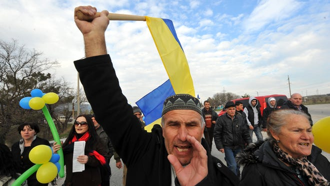 A member of the Crimean Tatar community holds the Ukrainian national flag during a demonstration rally in front of a Ukrainian military base in the town of Bakhchisarai, south of Simferopol.