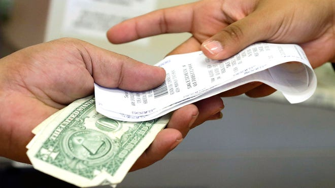 A cashier hands a customer his change and receipt during a transaction at a Sears store in Henderson, Nev.