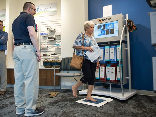 Matthew Martin helps Karen Bacon use the Aetrex foot scanner to see which inserts are going to take care of her needs at the ReNew shop inside the new Orthopedic and Neuroscience Hospital at Deaconess Gateway.