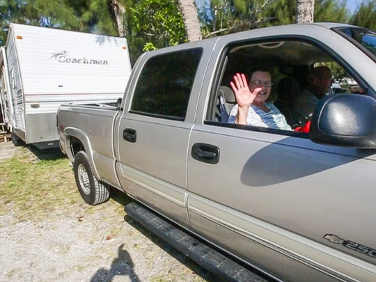Barbara waves goodbye as they pull away from the campsite. Waylon and Barbara Snead have spent the entire month of March at Sanibel's Periwinkle Park campground for the past 19 years. They departed with their travel trailer Friday morning, for their home in Raleigh North Carolina. They spent Friday morning packing up the last few things into the back of their pickup truck and trailer for the four-day journey. They will stop and visit friends and family along the way home. Shot on April 1, 2016.
