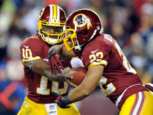 Washington running back Evan Royster, right, takes a handoff from quarterback Robert Griffin III during a game against Dallas on Dec. 30, 2012. Royter is a former Nittany Lion. (Associated Press)