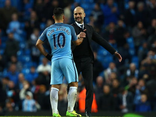 Manchester City's Sergio Aguero, left, shakes hands with Manchester City manager Pep Guardiola at the end of the English Premier League soccer match between Manchester City and Liverpool at the Etihad Stadium in Manchester, England, Sunday March 19, 2017. (AP Photo/Dave Thompson)