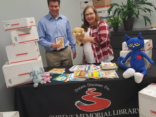 Every Child Ready to Read Children's Program Coordinator Julie Grice receives the book donation from David Wilson of the Rotary Club.