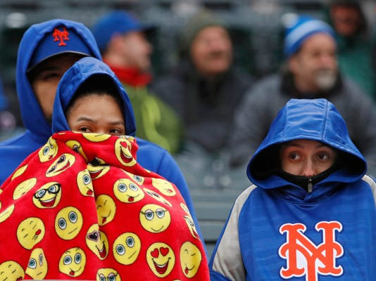 New York Mets fans bundle up against the cold in 40 degree temperatures during a baseball game between the New York Mets and the Milwaukee Brewers, Sunday, April 15, 2018, in New York. (AP Photo/Kathy Willens)