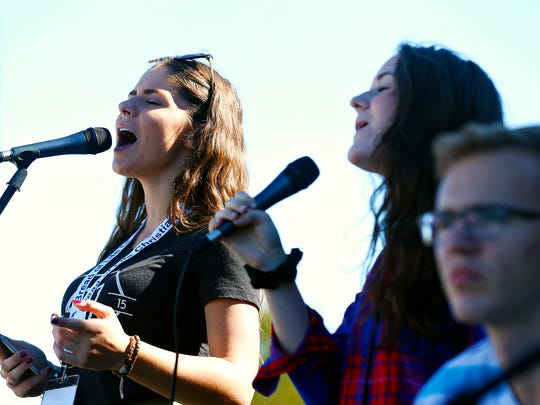 From left: Deana Vedernikov, 17, Sarah Illyuk, 17 and Tim Kozlov, 20, perform worship music during Bread of Life Christian Church's Russian Harvest Festival at the church grounds in Rogersville, Mo. on Oct. 22, 2016.