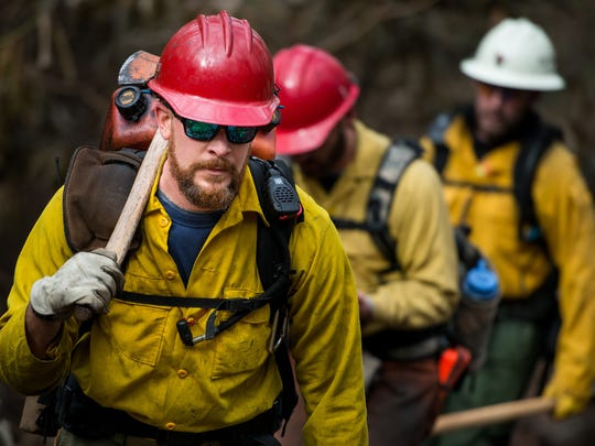 U.S. Forest Service firefighter Chad Heck, from the Colville National Forest in Washington state, hikes up the Rainbow Falls Trail in the Great Smoky Mountains National Park near Gatlinburg, Tenn., Wednesday, Dec. 7, 2016. Hundreds of firefighters continue to conduct operations within the park as the Chimney Top 2 Fire is reported to be 64% contained as of Wednesday morning.