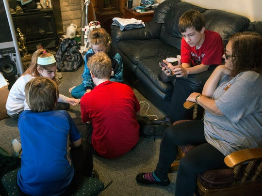 Brenda Nichols sits surrounded by some of her grandchildren she is raising in her Valley Station home. 12/22/17