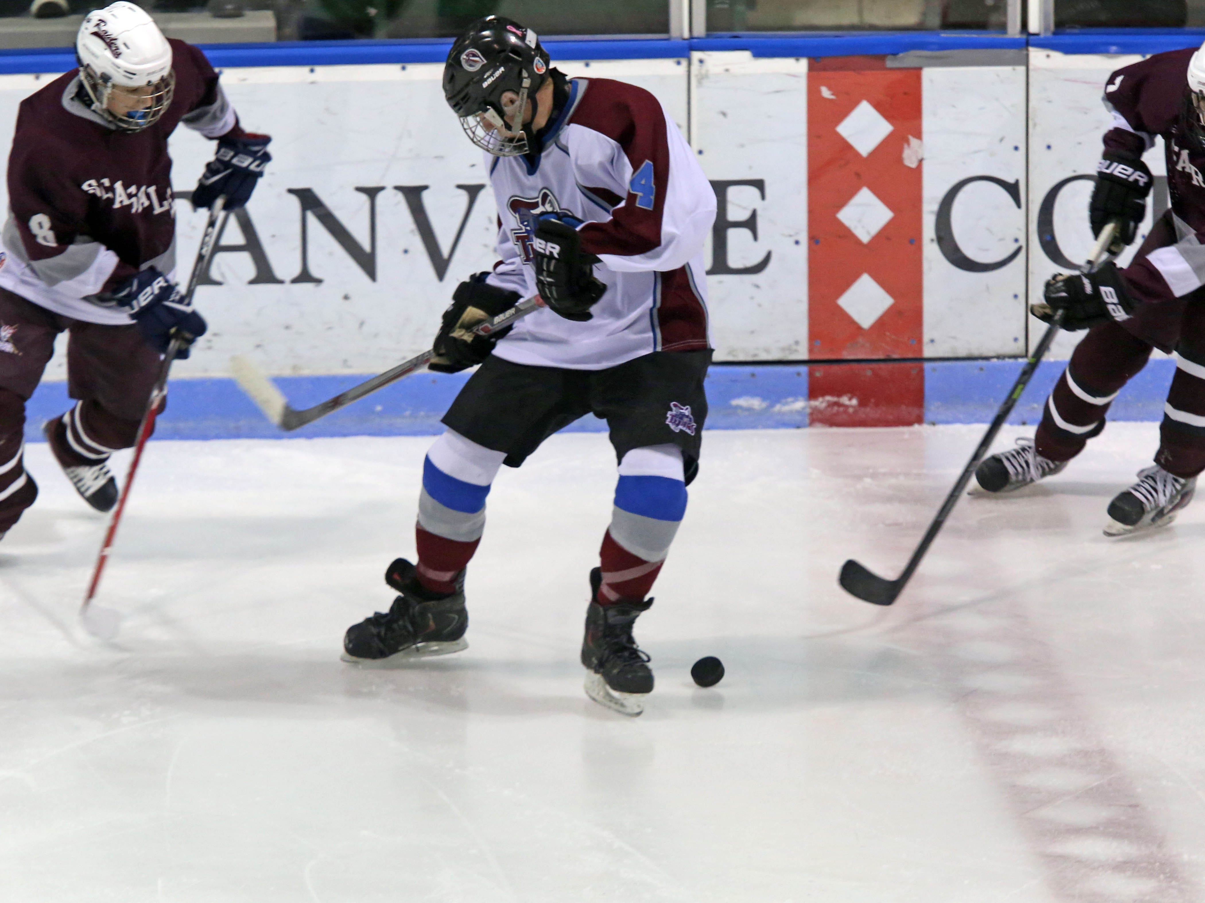 Scarsdale's Robert Kramer, left, and Brandon Bank try to steal the puck from Rye Town/Harrison's Ike Murov during Monday's game at Rye Playland.