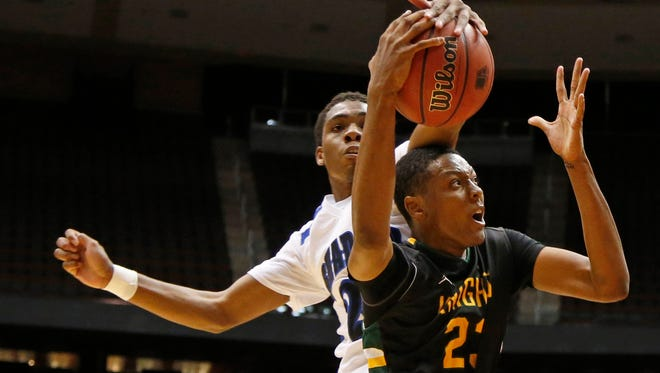 Shadow Mountain's J.J. Rhymes, fouls Gilbert Christian's Cameron Satterwhite, #23, during the Division II boys basketball semifinals at Arizona Gila River Arena in Glendale on February 28, 2015.