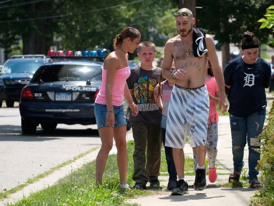 Residents of the Baker/Donora neighborhood leave the scene where Lansing police and Ingham County sheriff deputies apprehended a suspect after a car and subsequent foot chase on Sunday, July 30, 2017.