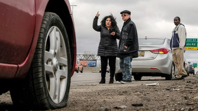 Sylvia Campos of Detroit gets upset while watching traffic from the side of northbound I-75 near the McNichols Road exit with her boyfriend Rolando Lopez of Saginaw, after hitting a pothole that left her front passenger side tire flat on Wednesday, February 21, 2018 in Detroit. Campos was on her way to a funeral in Toledo.