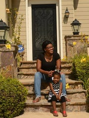 KAREN QUINCY LOBERG/THE STAR Micquel Brown and her daughter Micayla, 3, sit on the front steps of their new home in Newbury Park.