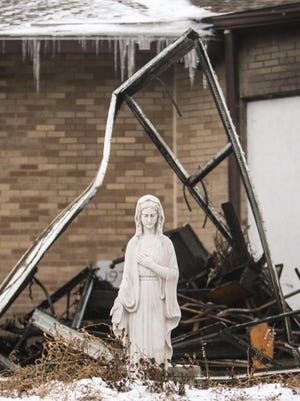 A statue of St. Mary stands near the fire debris