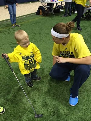 Michigan senior Lauren Grogan, right, offers some pointers to a young golfer at a previous event.