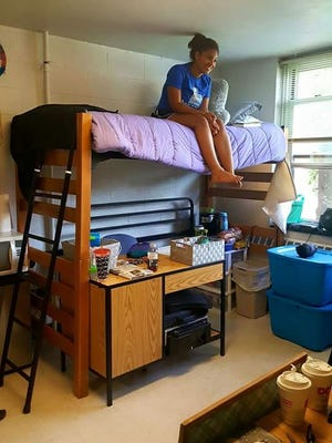 Farrah Gillie poses in her dorm room at Western Carolina University. The 18-year-old Hendersonville resident grew up in foster care and started her freshman year at the school in August.