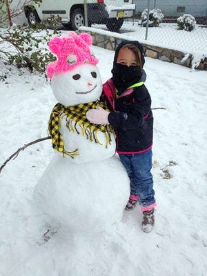 Five-year old Ryan Isabella Saenz took advantage of the snow by building a snowman over the weekend in Silver City. According to the National Weather Service, more snow was a possibility Early Tuesday morning.