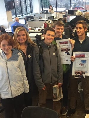 Student journalists from the Burlington High School Register stand in the Burlington Free Press news room with one of their editors, Alexandre Silberman, who is third from the left.