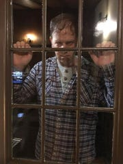 One of the movie's villains, played by Bryan Chesters, peers at a window during filming.