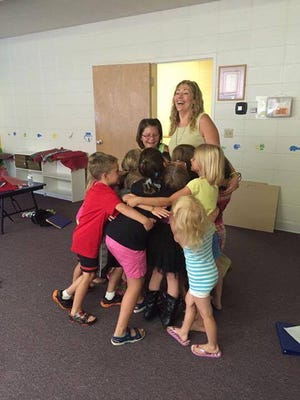 Theresa Menting gets a group hug after a successful music and theater workshop with Fond du Lac youth.