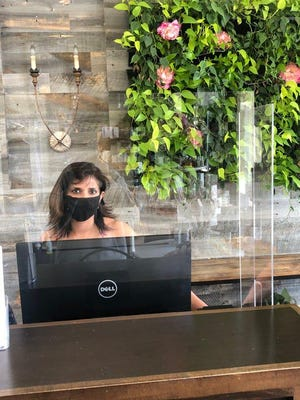 Woodhouse Day Spa owner Anju Brodbine greets customers from behind a plexiglass shield at the front desk.