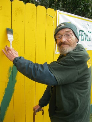 Friedrich Harrsch is the owner of the signature green-and-gold fence at 1177 Shadow Lane that's visible along Lombardi Avenue across from Lambeau Field. It will get its new slogan for the 2014 Green Bay Packers season on Labor Day.