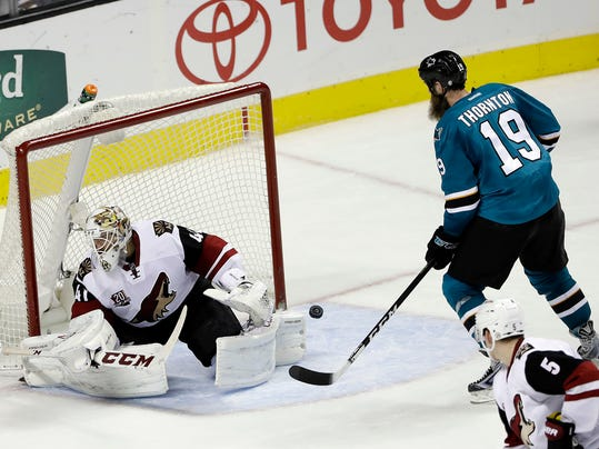 Arizona Coyotes goalie Mike Smith, left, is beaten for the game-winning goal on a shot from San Jose Sharks Brent Burns, not seen, as Sharks' Joe Thornton (19) watches during overtime of an NHL hockey game Tuesday, Nov. 29, 2016, in San Jose, Calif. San Jose won 2-1. (AP Photo/Marcio Jose Sanchez)