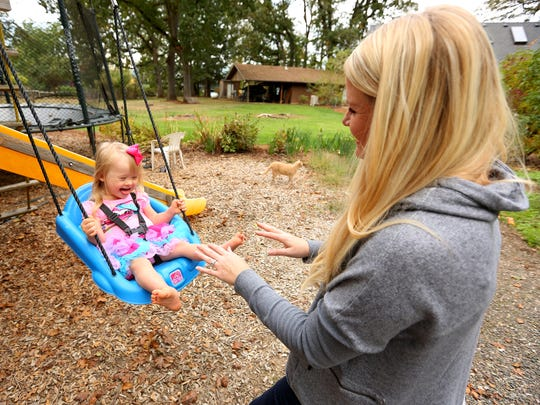 Ellie Stafford, 2, laughs while swinging with her mother Tiffany Stafford at their home, Friday, October 16, 2015, in Aurora, Ore. Ellie, who has Down syndrome, is redefining beauty by modeling and acting.