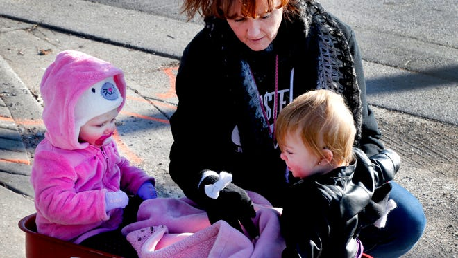 Michelle DeBerry bundles up her friend's children (left) Lenix and Harlow in a red wagon before going for a stroll in downtown Murfreesboro to get out of house on Tuesday.