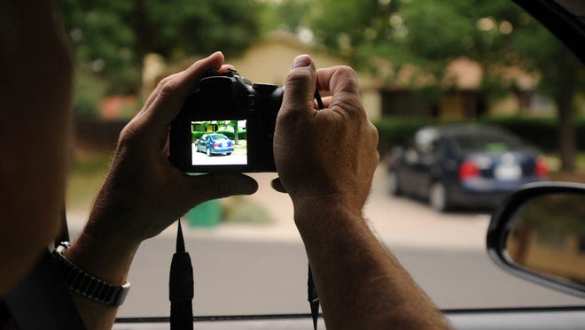 Dale Wood, the city of Fort Collins compliance inspector, photographs a car at a house under investigation of violating the city's over-occupancy ordinance in this 2012 file photo.
