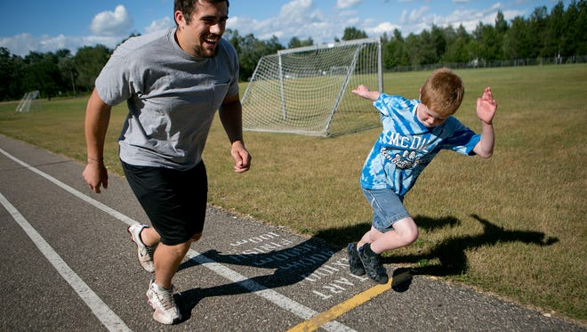 Little Brother Alex Slowinski, 9, of Plover challenged his Big Brother Zach Lentz, left, to a race around the track at the Plover-Whiting Elementary School playground in Plover, Thursday, July 30, 2015.