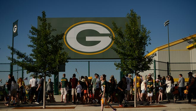 Fans watch along the fence line during the Green Bay Packers training camp at Ray Nitschke Field on Thursday, July 30, 2015.