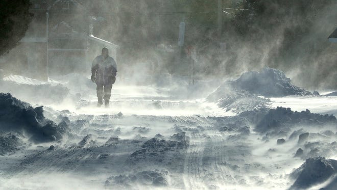 A pedestrian walks through blowing snow along Stites Avenue in Cape May Court House, N.J.