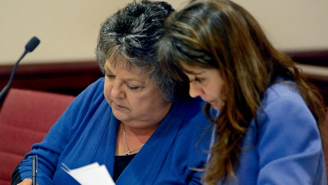 Former New Mexico Secretary of State Dianna Duran, left, signs an amended plea deal alongside her attorney Erlinda Johnson in District Judge Glenn Ellington's court on Friday in Santa Fe.