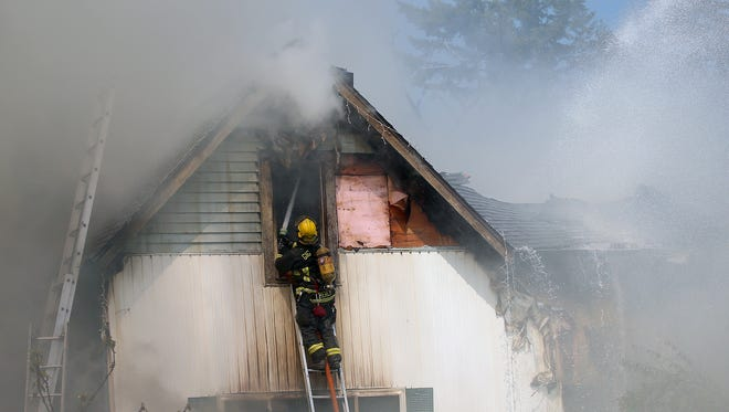 A Gig Harbor firefighter works at a two-alarm house fire on Goldenrod Street in Port Orchard on Friday.