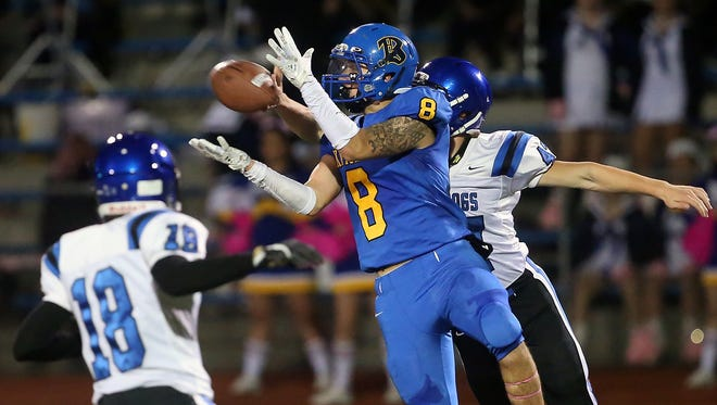 Bremerton's Savante Perrigo (center) makes a catch while under pressure by North Mason's Cole Varick (left) and Reese Smelcer (right) at Bremerton Memorial Stadium on Friday, October 27, 2017. Perrigo ran the ball into the end zone for a touchdown.