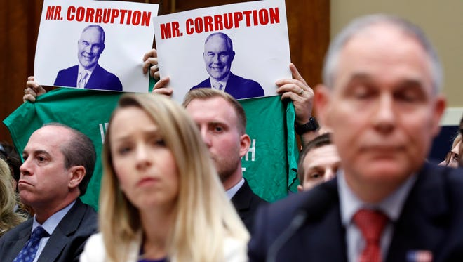 Protesters behind EPA Administrator Scott Pruitt at his congressional hearing on April 26, 2018.