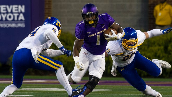 South Dakota State safety Nick Farina, left, and South Dakota State defensive end Ryan Earith (90) tackle James Madison running back Trai Sharp (1) during the first half of a FCS semifinals football game, Saturday, Dec. 16, 2017 in Harrisonburg.