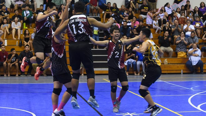 The Father Duenas Friars celebrate their Independent Interscholastic Athletic Association of Guam boys' volleyball championship win over the George Washington Geckos at Southern High School Gym in Santa Rita on May 14.