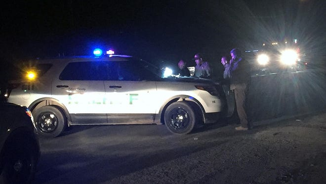 Tulare County Sheriff's deputies and detectives coordinate a search for evidence Friday night in an Earlimart neighborhood after an adult male and a teenage boy were shot there.